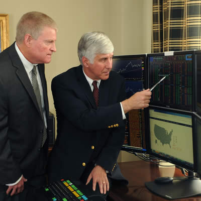 Herb Diamant and Kevin Jakeway pointing to charts on computer monitors